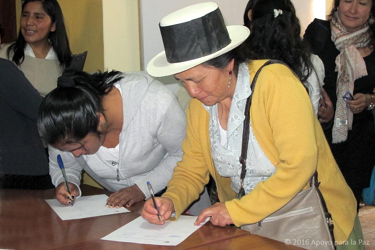 Los asistentes firman el acta. En la foto Adelina García, Presidenta de ANFASEP.