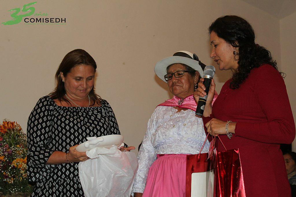 Janet Matta (COMISEDH) y mamá Sergia Flores (ANFASEP) entregan el reconocimiento a la Ministra